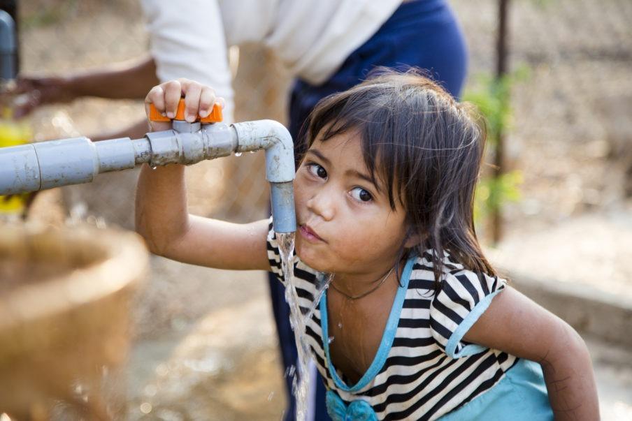 Kind trinkt Wasser aus einem Wasserhahn